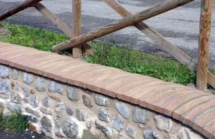 Sezione di muretto di cinta rivestito con copertine da muro